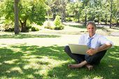 Full length portrait of mature businessman with laptop sitting on grass in park