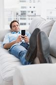 Happy man lying on the couch sending a text at home in the living room