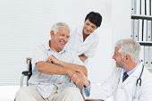 Happy senior patient and doctor shaking hands in the medical office