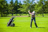 stock photo of swing  - Mature Golfer on a Golf Course Taking a Swing in the Fairway - JPG