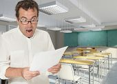 Horrified teacher reading a paper