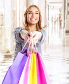 Happy girl with colorful shopping bag, cheerful young female doing purchase in great luxury retail s