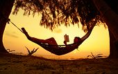 stock photo of rest-in-peace  - Young lady reading the book in the hammock on tropical beach at sunset - JPG