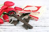 Key to love and happiness. Composition with key, decorative bag and flowers. Conceptual photo. On co