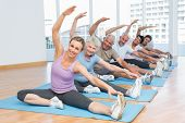 picture of senior class  - Happy female trainer with class stretching hands at yoga class - JPG