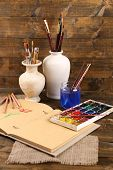 Composition with colorful watercolors, brushes in vase and sketcher on wooden background