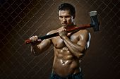 stock photo of ax  - the beauty muscular worker chopper man with big heavy ax in hands tired appearance on netting fence background - JPG