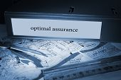 The word optimal assurance on blue business binder on a desk