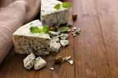 Tasty blue cheese with olives and basil, on wooden table