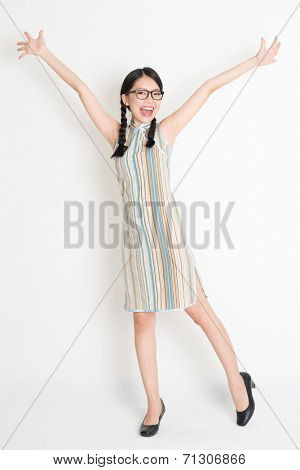 Portrait of full length Asian Chinese girl arms outstretched and looking at camera, in old-fashioned style cheongsam, standing on plain background.
