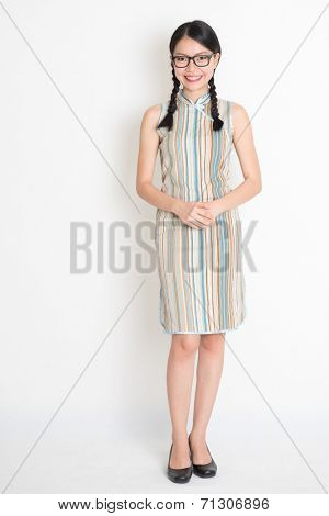 Portrait of full length Asian Chinese girl smiling and looking at camera, in retro revival style cheongsam, standing on plain background.