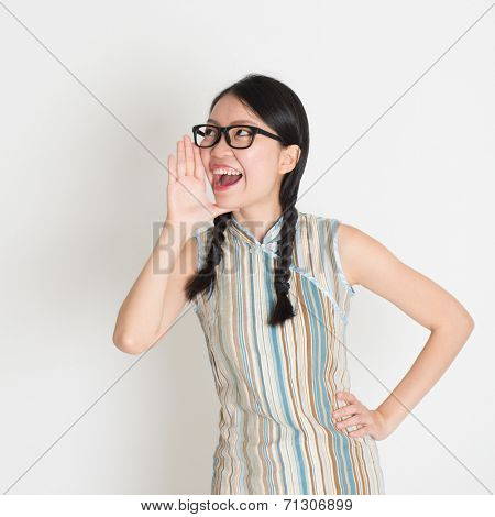 Portrait of Asian Chinese female  shouting loud, hand next to the mouth, in retro revival style cheongsam standing on plain background.