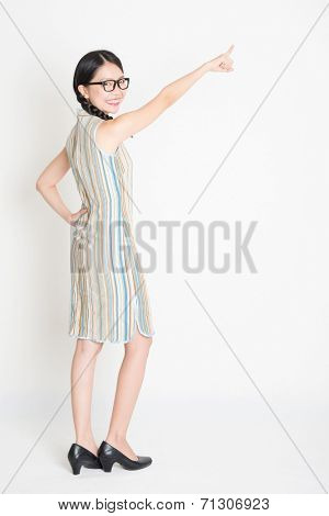 Portrait of rear view full length Asian Chinese girl pointing on blank copy space and looking at camera, in retro revival style cheongsam, standing on plain background.