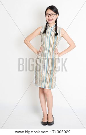 Portrait of full length Asian Chinese girl hands on waist and looking at camera, in retro revival style cheongsam, standing on plain background.