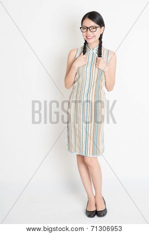 Portrait of old-fashioned Asian Chinese girl in traditional cheongsam or qipao dress smiling, full length standing on plain background.