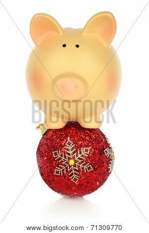 Piggy bank balancing on a Christmas ball