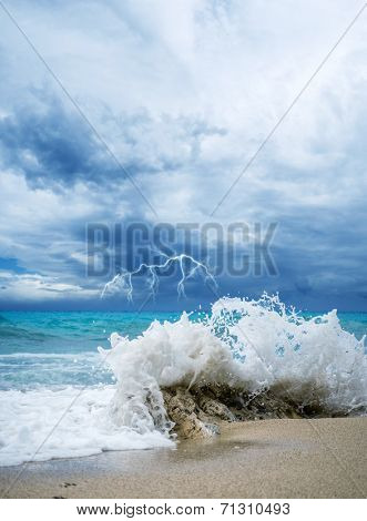 waves breaking on a stony beach during a thunderstorm with lightning