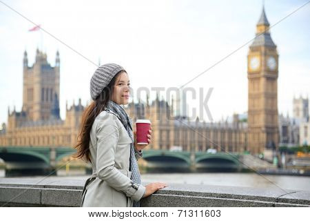 London woman drinking coffee by Westminster Bridge. Young female professional business woman in London, England. Beautiful young multiracial Asian Caucasian girl.