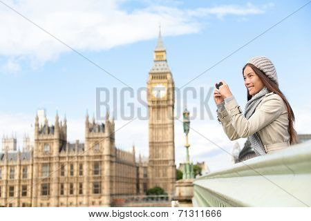 Travel tourist in london sightseeing taking photo pictures near Big Ben. Woman holding smart phone camera smiling happy near Palace of Westminster, Westminster Bridge, London, England