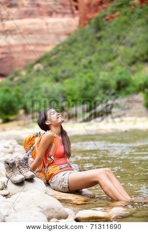 Relaxing hiker woman resting feet in river happy serene and relaxed afterhiking in Zion National Park. Female hiker in Zion Canyon wearing backpack. Healthy lifestyle multiracial Asian girl, Utah, USA