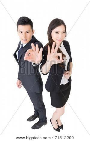 Attractive Asian business woman and man give you an okay sign, full length portrait isolated on white.