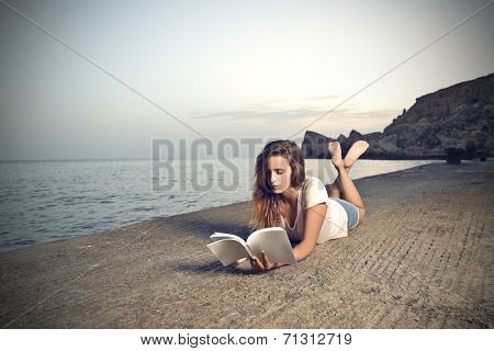 young woman who is lying on a pier and she is reading a book