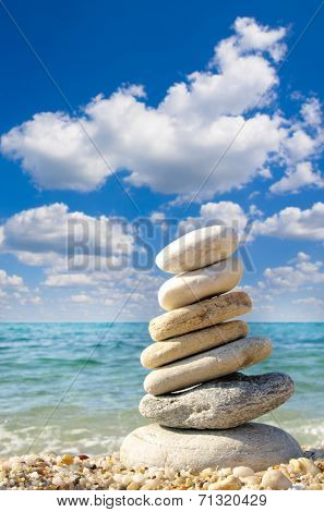 stones balanced on top of eachother on a sandy beach