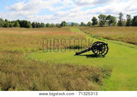 Old artillery weapon set in meadow