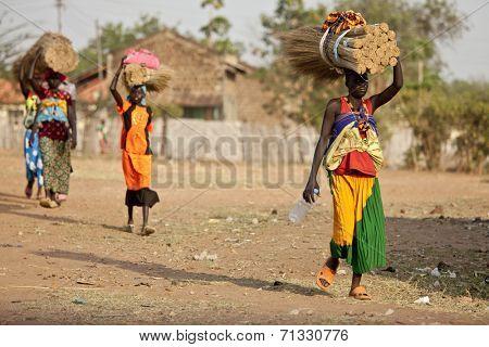 TORIT, SOUTH SUDAN-FEBRUARY 20 2013: Unidentified women carry heavy load on their heads in Torit, South Sudan.
