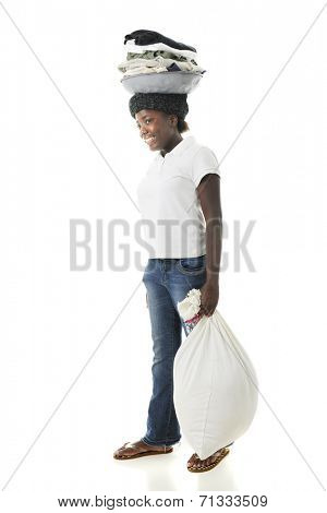A Haitian preteen happily hauling laundry on her head while carrying a full back in her hand.  On a white background.