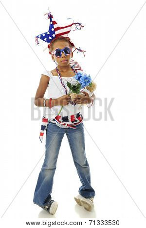 A young elementary girl whose decked herself out for the Fourth of July.  On a white background.