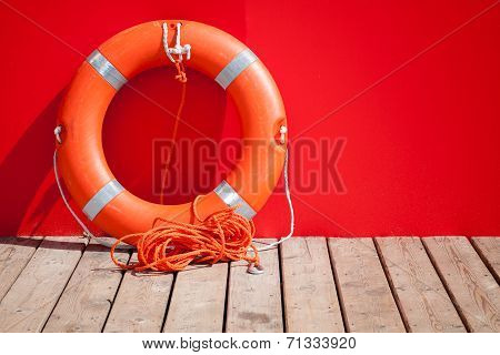 Lifebuoy Stands On Wooden Floor Nearby Red Wall Of Lifeguard Station