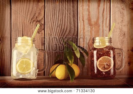 Glasses of lemonade and sweet tea with lemons on a ledge in front of a rustic wooden kitchen wall. The mason jar style glasses have handles and drinking straws. Instagram Style with vignette.