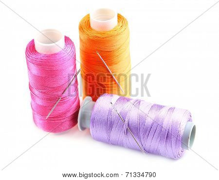 Needles and spools of thread isolated on white