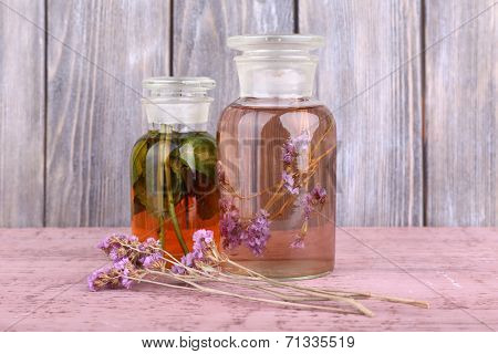 Bottles of herbal tincture and brunch of flowers on a wooden table in front of wooden wall