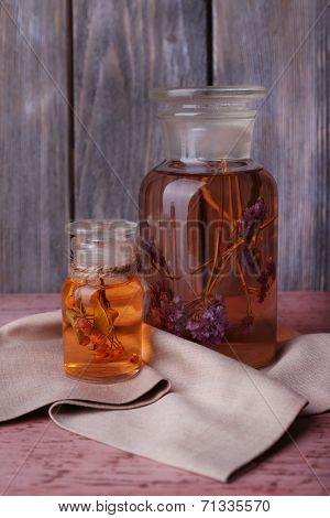 Bottles of herbal tincture on a wooden table in front of wooden wall
