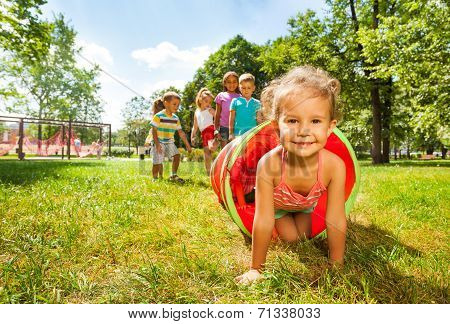 Cute group of kids play crawling in tube