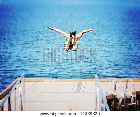 a boy jumping of an old dock into a pond