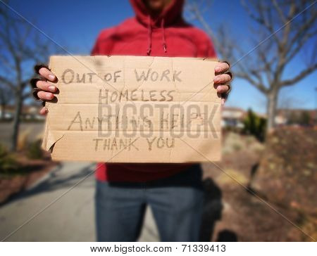 a begging homeless person with a sign on a cold sunny winter day