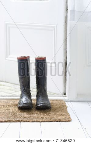 Muddy wellington boots on door mat