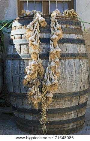 String of garlic hanging from wooden cask