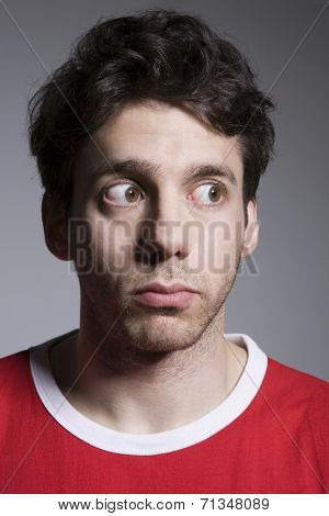 A suspicious young male looking sideways isolated over grey background