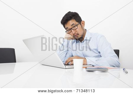 Portrait of bored businessman sitting with laptop at desk in office