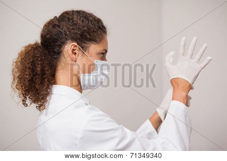 Dentist putting on surgical gloves at the dental clinic