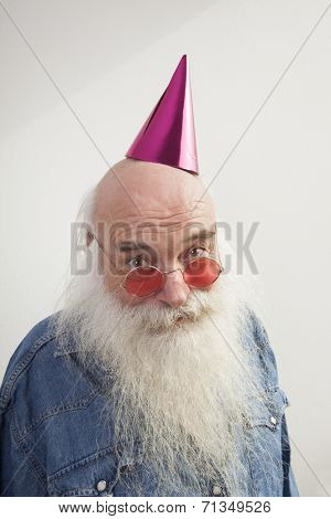 Portrait of senior man wearing red glasses and party hat against gray background