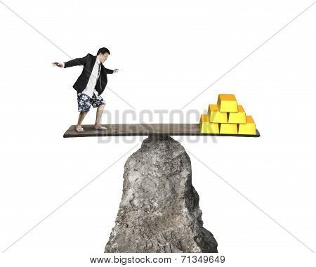 Man Standing On Rocky Seesaw Vs Stack Of Gold