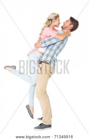 Handsome man picking up and hugging his girlfriend on white background
