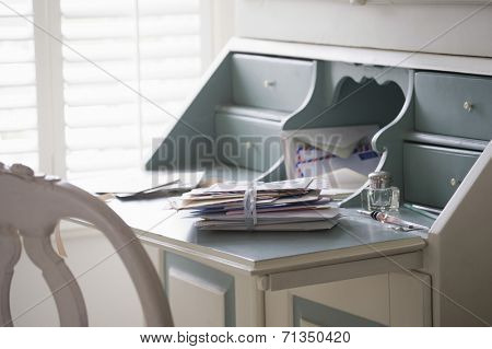 Letters tied up on writing desk at home