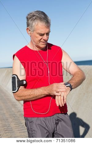 Active senior man jogging on the pier on a sunny day