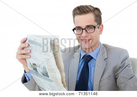 Nerdy businessman reading the newspaper on white background